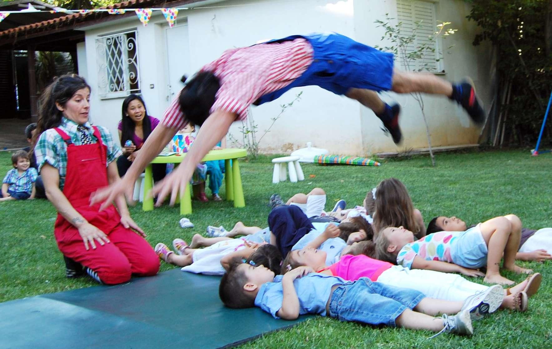 Καλλιτέχνης του τσίρκο πετάει πάνω από ξαπλωμένα παιδιά σε παιδικό πάρτυ