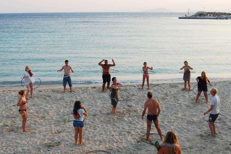 Δέκα μαθητές ακολουθούν οδηγίες της δασκάλας σε μάθημα χούλα χουπ σε παραλία στη Δονούσα στη διάρκεια του φεστιβάλ Donousa Juggling Weekend.