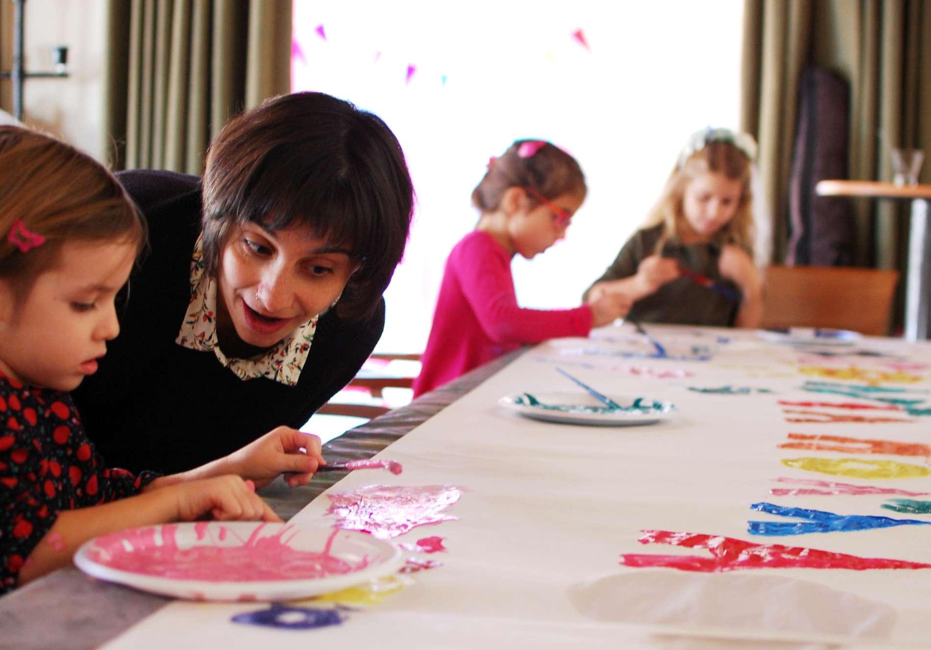 Ανιματέρ και παιδιά σε εργαστήρι ζωγραφικής σε παιδικό πάρτυ