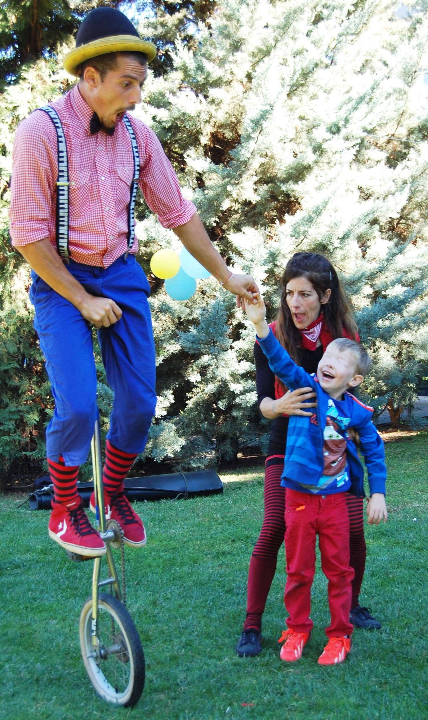 Ανιματέρ χρησιμοποιεί τη βοήθεια παιδιού από το κοινό παιδικού πάρτυ για να ισορροπήσει πάνω σε ψηλό μονοποδήλατο