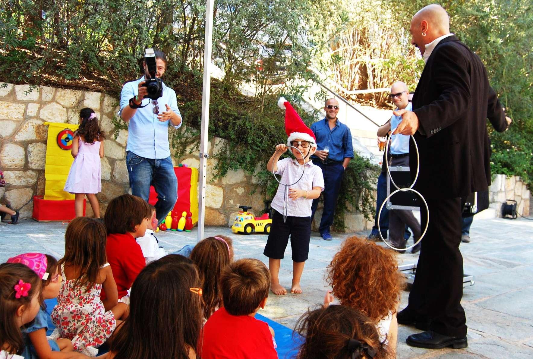 Ταχυδακτυλουργός με εθελοντή παιδί από το κοινό προσφέρει θέαμα σε πάρτυ βάφτισης