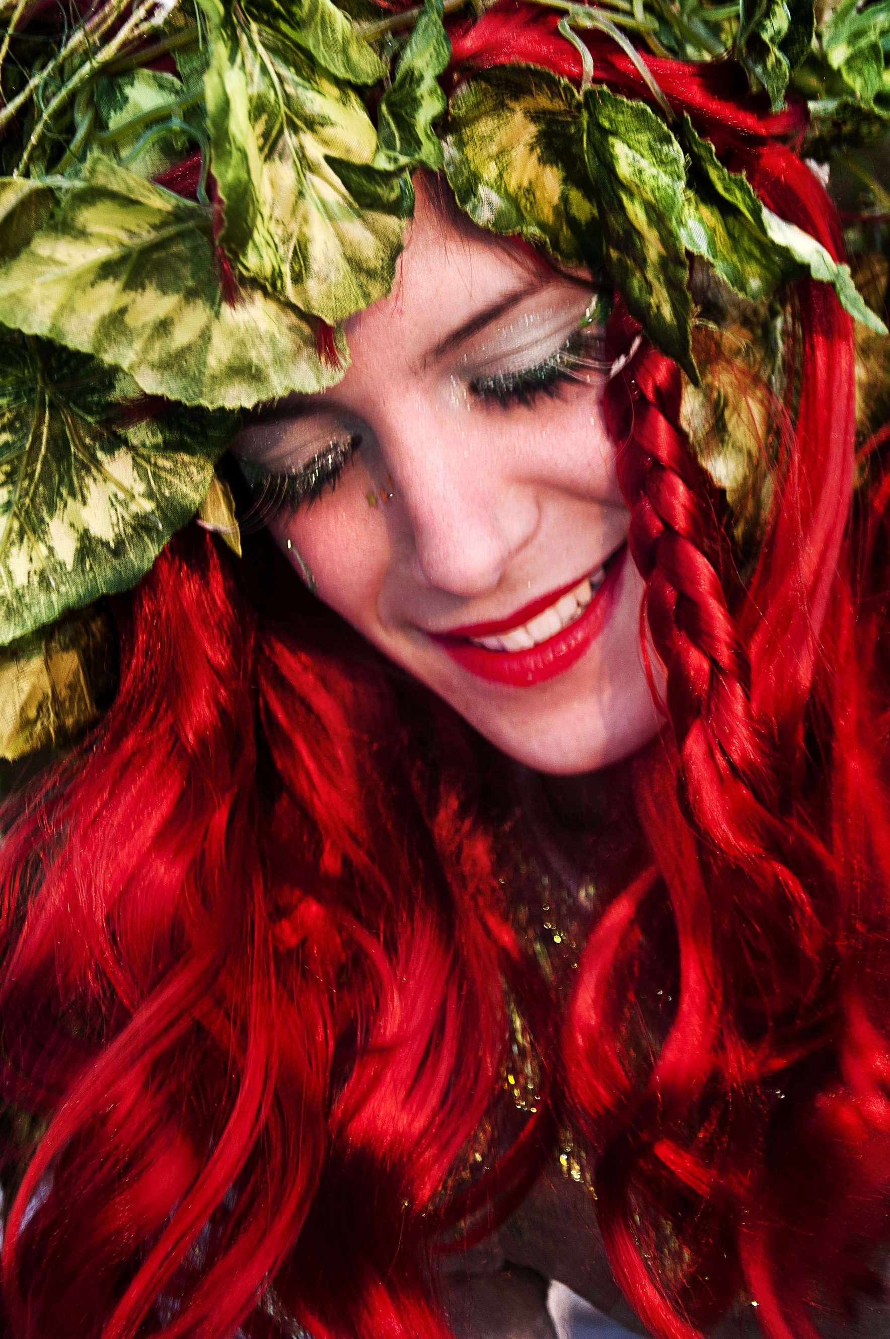 Ανιματέρ ντυμένη γοργόνα με κόκκινα μαλλιά και στεφάνι από φύλλα