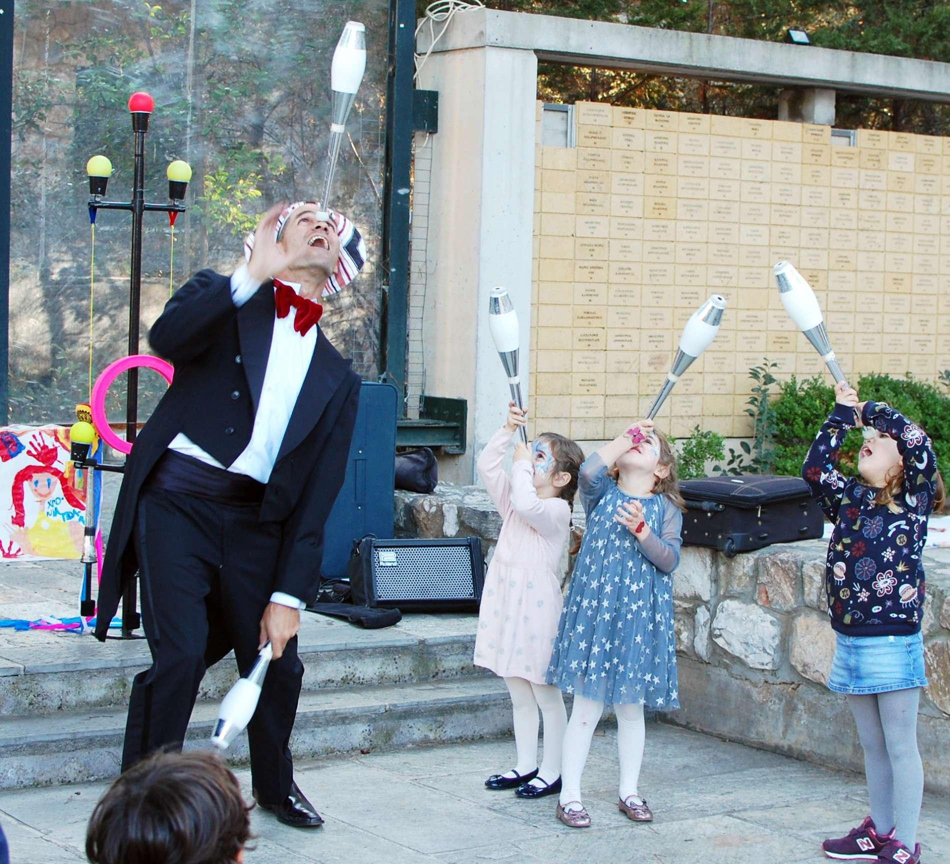 Ζογκλέρ και παιδιά σε παιδικό πάρτι ισορροπούν κορύνες στη μύτη τους στη διάρκεια ενός fundastick circus party