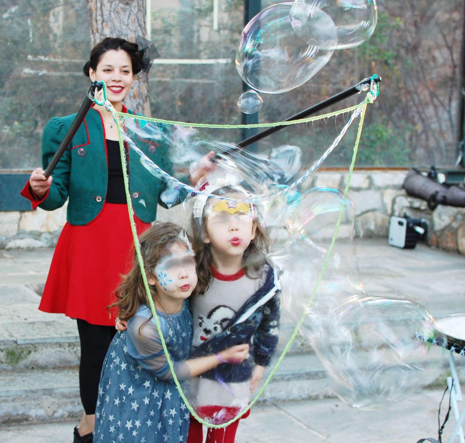 Δύο κορίτσια φτιάχνουν μεγάλες σαπουνόφουσκες φυσώντας ειδικό εξάρτημα που κρατά ανιματέρ σε παιδικό πάρτυ.