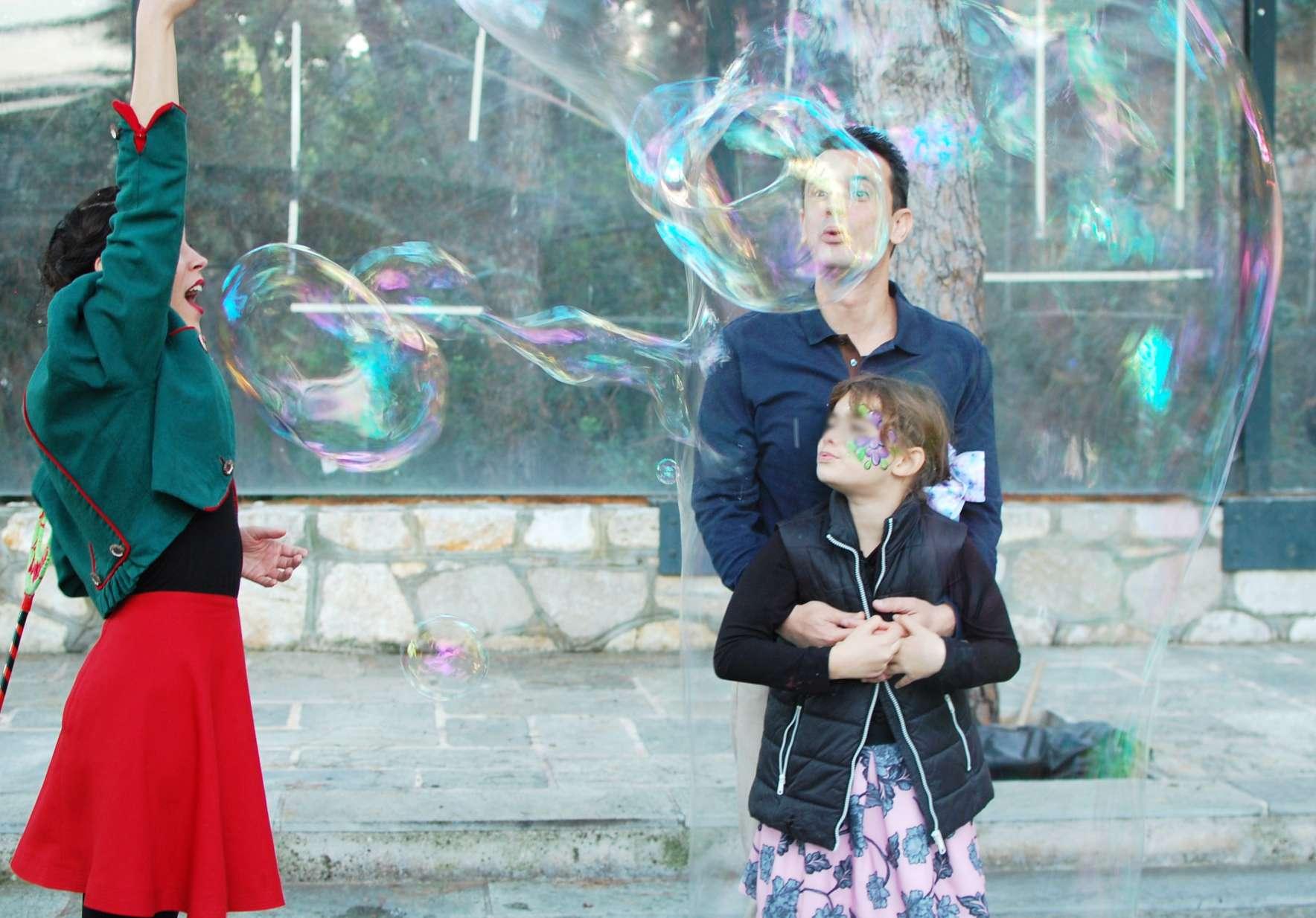 Μπαμπάς και κόρη φυσάνε σαπουνόφουσκες μέσα από τεράστια σαπουνόφουσκα σε παιδικό πάρτυ.