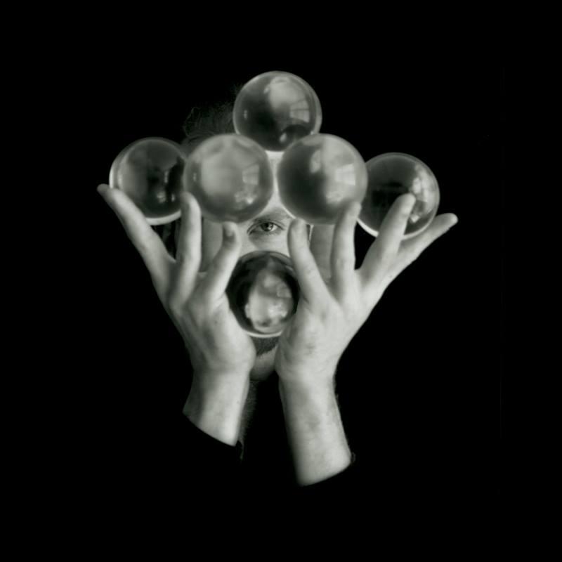 Ζογκλέρ σχηματίζει όμορφο σχήμα κρατώντας πολλές κρυστάλλινες μπάλες στα χέρια του