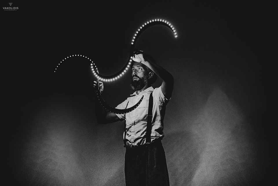 Ζογκλέρ παίζει στο σκοτάδι με φωτεινά αντικείμενα (κοντάρια σε σχήμα S)