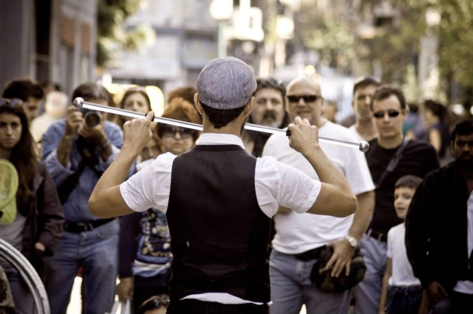 Ζογκλέρ προσφέρει θέαμα καθώς χειρίζεται μπατόν μπροστά σε κοινό σε θέατρο δρόμου.