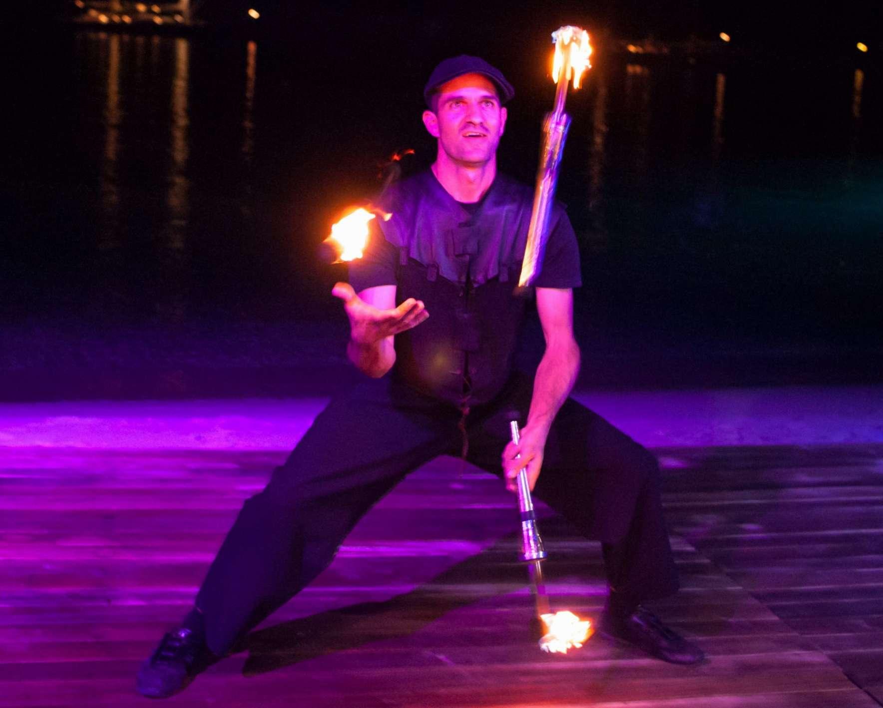 Ζογκλέρ παίζει με τρεις αναμμένους πυρσούς σε εταιρική εκδήλωση στο Budha Bar της Μυκόνου.