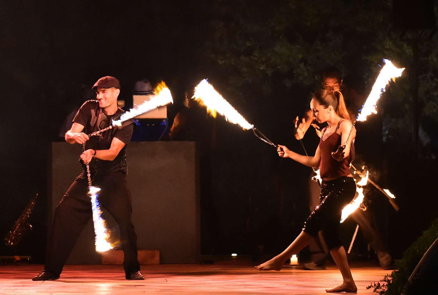 Χαρούμενοι καλλιτέχνες παίζουν με φλεγόμενα σχοινιά σε σώου με φωτιές πάνω σε σκηνή, σε εκδήλωση γάμου στο ξενοδοχείο Amanzoe.