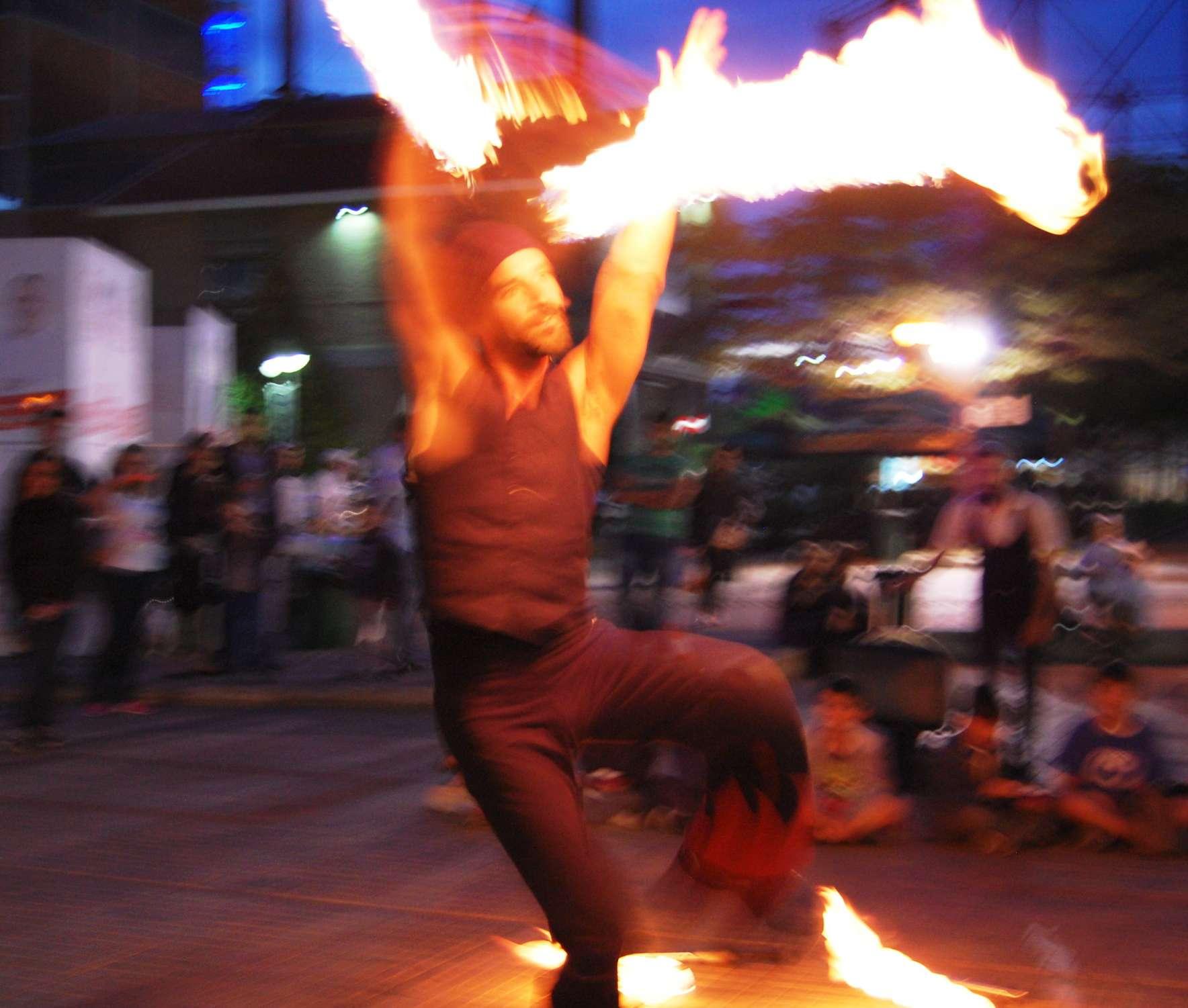 Ζογκλέρ χορεύει παίζοντας με δύο κοντάρια με φωτιές σε φεστιβάλ στην Τεχνόπολη στην Αθήνα.