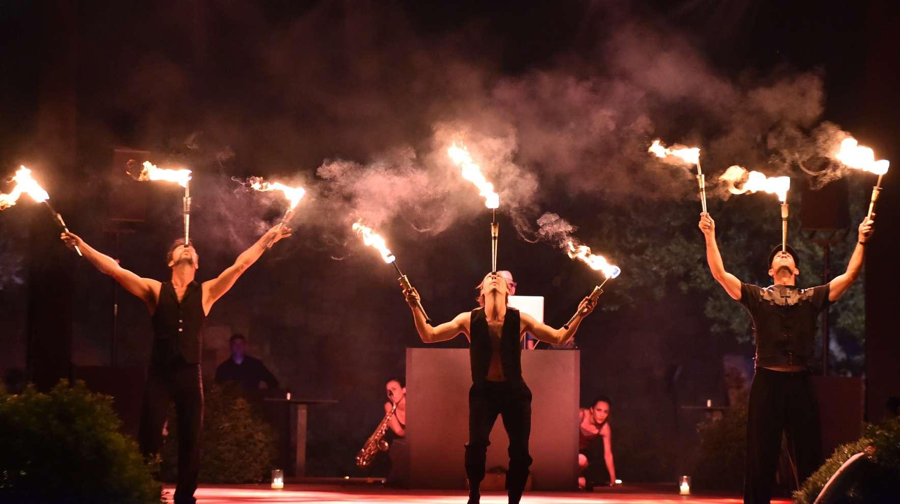 Σώου με φωτιές με τρεις ζογκλέρ να ισορροπούν αναμμένους πυρσούς στη σκηνή γαμήλιας δεξίωσης στο ξενοδοχείο Amanzoe.