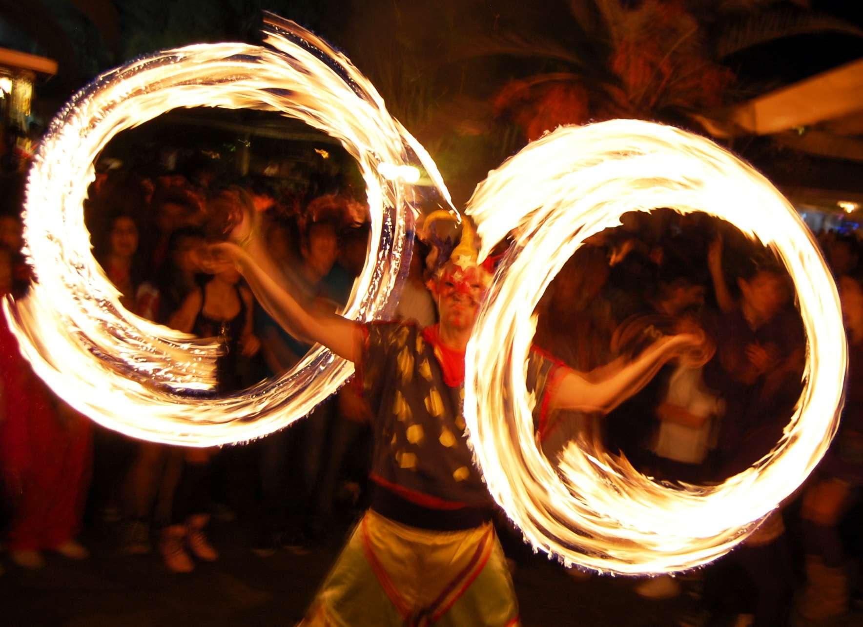 Ζογκλέρ παίζει με δύο κοντάρια με φωτιές δημιουργώντας δύο φωτεινούς κύκλους σε αποκριάτικο πάρτι στο Κέντρο Ιππόκαμπος στη Χαλκίδα.