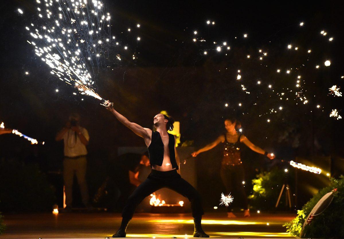 Ζογκλέρ χειρίζεται πυροτέχνημα σε σώου με φωτιές σε εκδήλωση γάμου στο ξενοδοχείο Amanzoe.