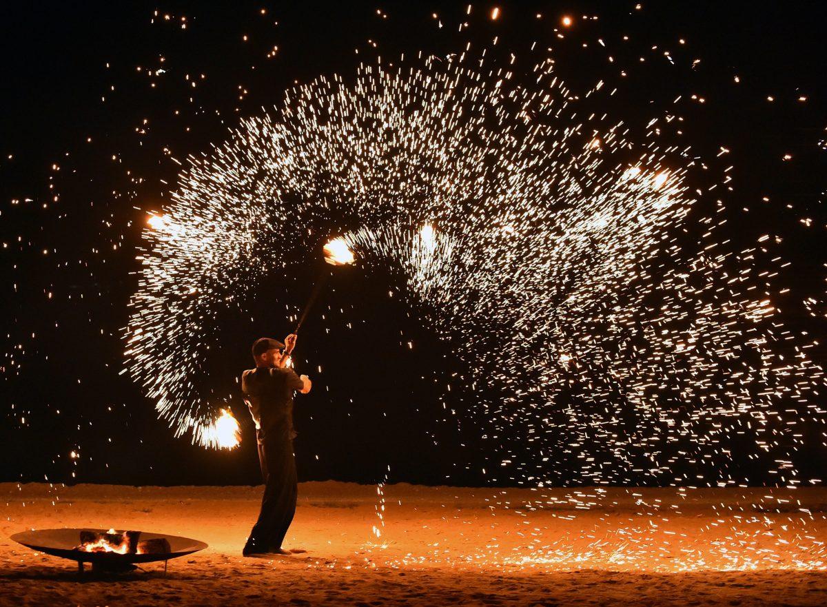 Ζογκλέρ δημιουργεί εφέ πυροτεχνήματος σε γαμήλια δεξίωση στην παραλία του ξενοδοχείου Amanzoe.