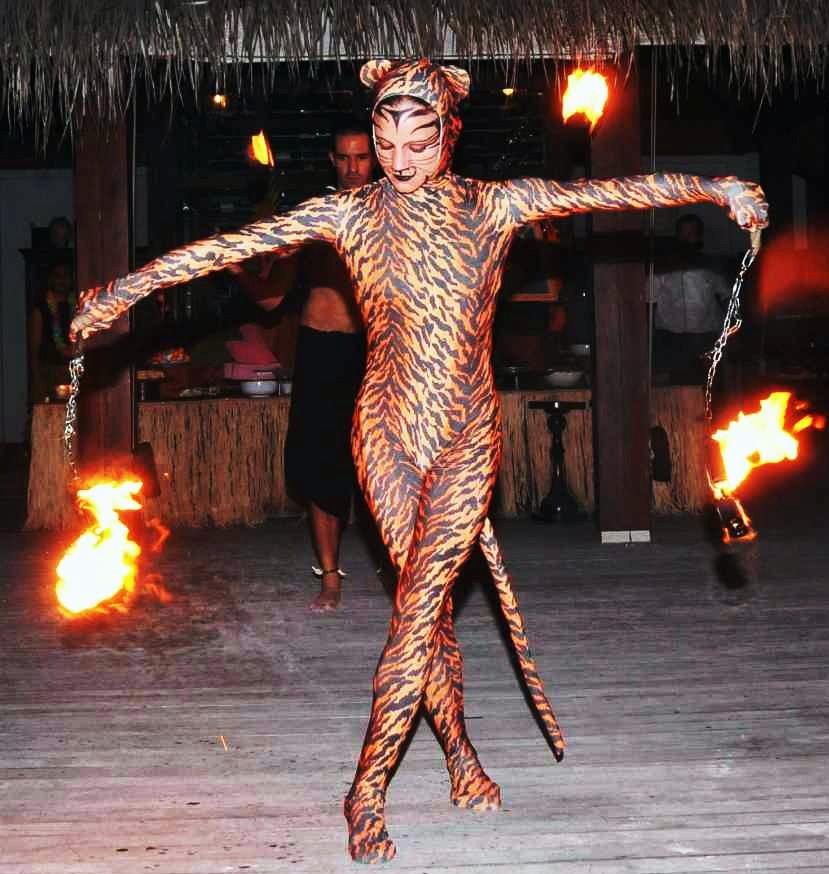 Χορεύτρια ντυμένη αγριόγατα παίζει με αναμμένες αλυσίδες σε πάρτι γάμου.