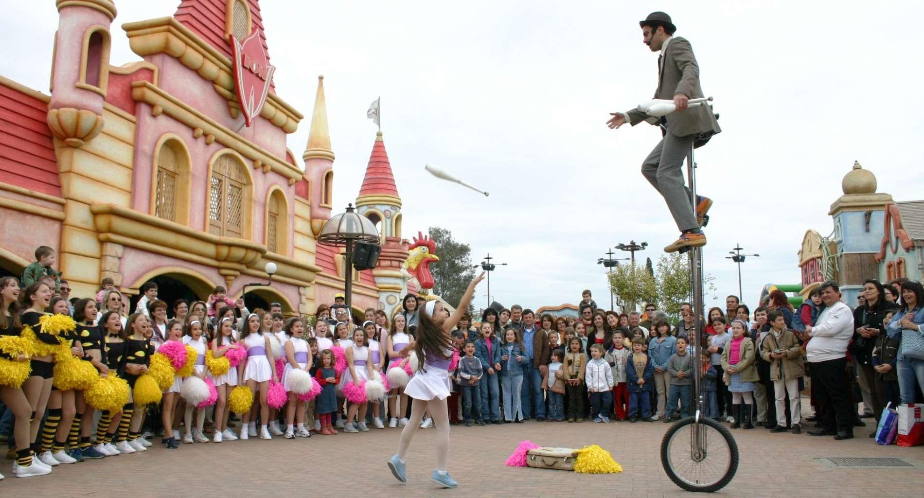 Ζογκλέρ πάνω σε ψηλό μονοποδήλατο, παίζει πάσες με κορύνες με κορίτσι μπροστά σε μεγάλο κοινό σε λούνα παρκ