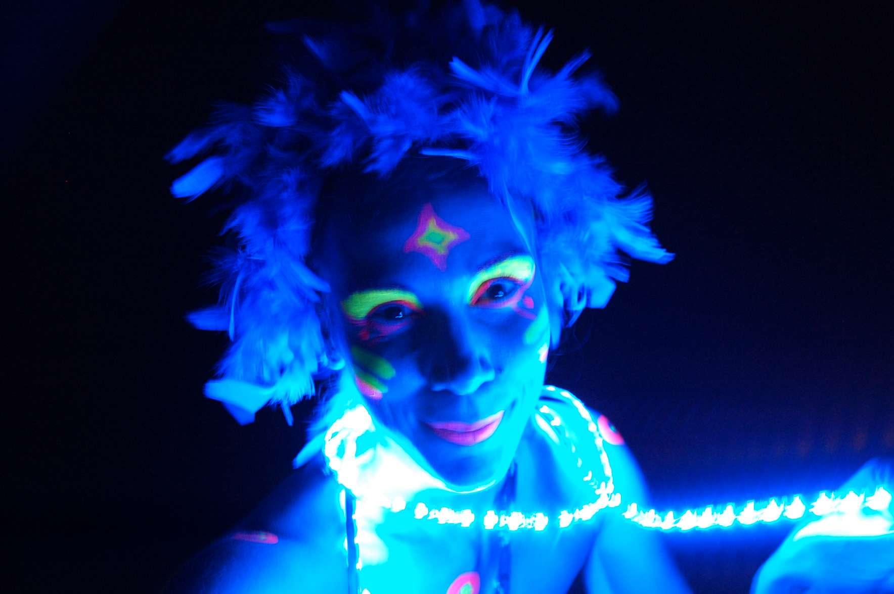 Ανιματέρ με φωσφοριζέ μακιγιάζ και αυτόφωτο κολιέ χαμογελάει σε ιδιωτικό πάρτυ