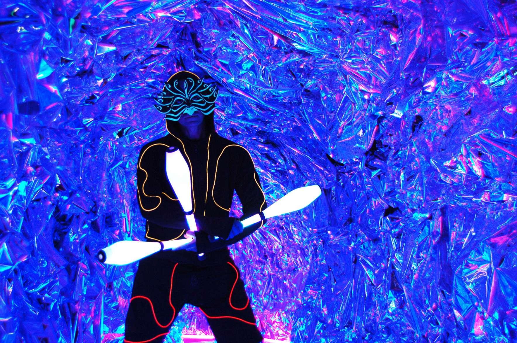 Ζογκλέρ με φωτεινό κοστούμι και μάσκα που φωσφορίζει κρατάει τρεις φωτεινές κορύνες σε ιδιωτικό πάρτυ