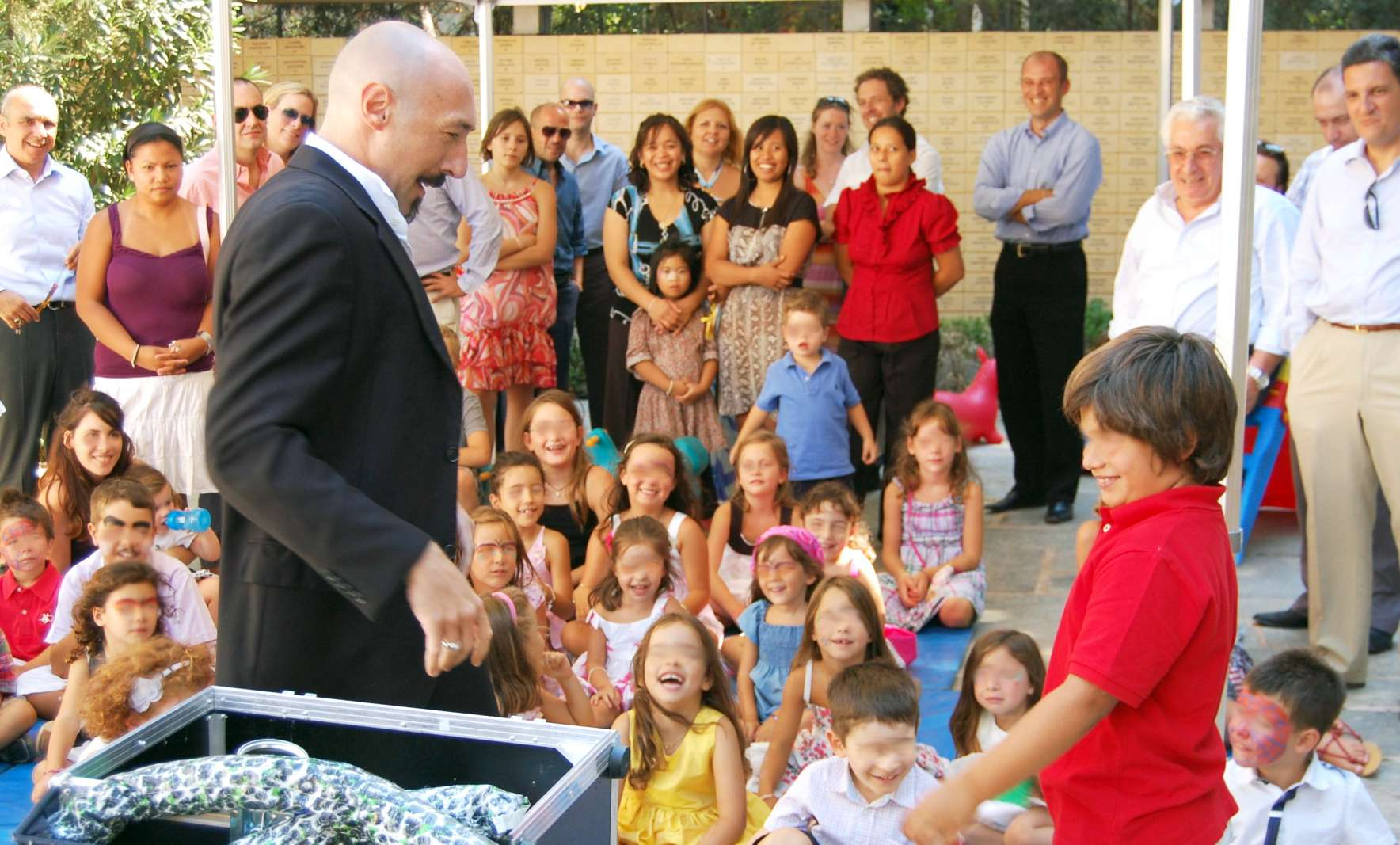 Magician entertaining adults and children at a children party.