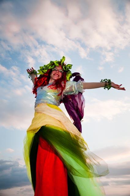 Γελαστή ξυλοπόδαρη με πολύχρωμο φόρεμα, με τα χέρια ανοιχτά προς τον ουρανό