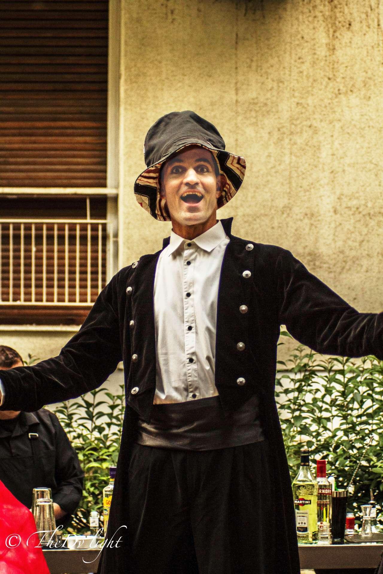 Γελαστός ξυλοπόδαρος με φράκο και ψηλό καπέλο υποδέχεται καλεσμένους με ανοικτά χέρια σε εκδήλωση