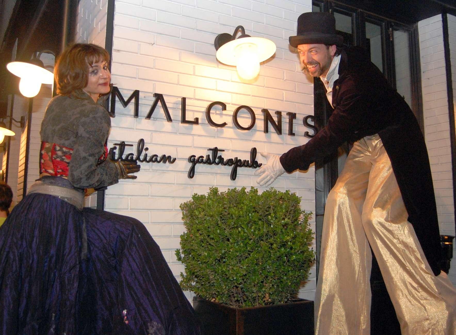 Χαμογελαστό ζευγάρι άντρα και γυναίκας ξυλοπόδαρων δείχνουν την επιγραφή με το όνομα του εστιατορίου Malconi's σε εκδήλωσή του