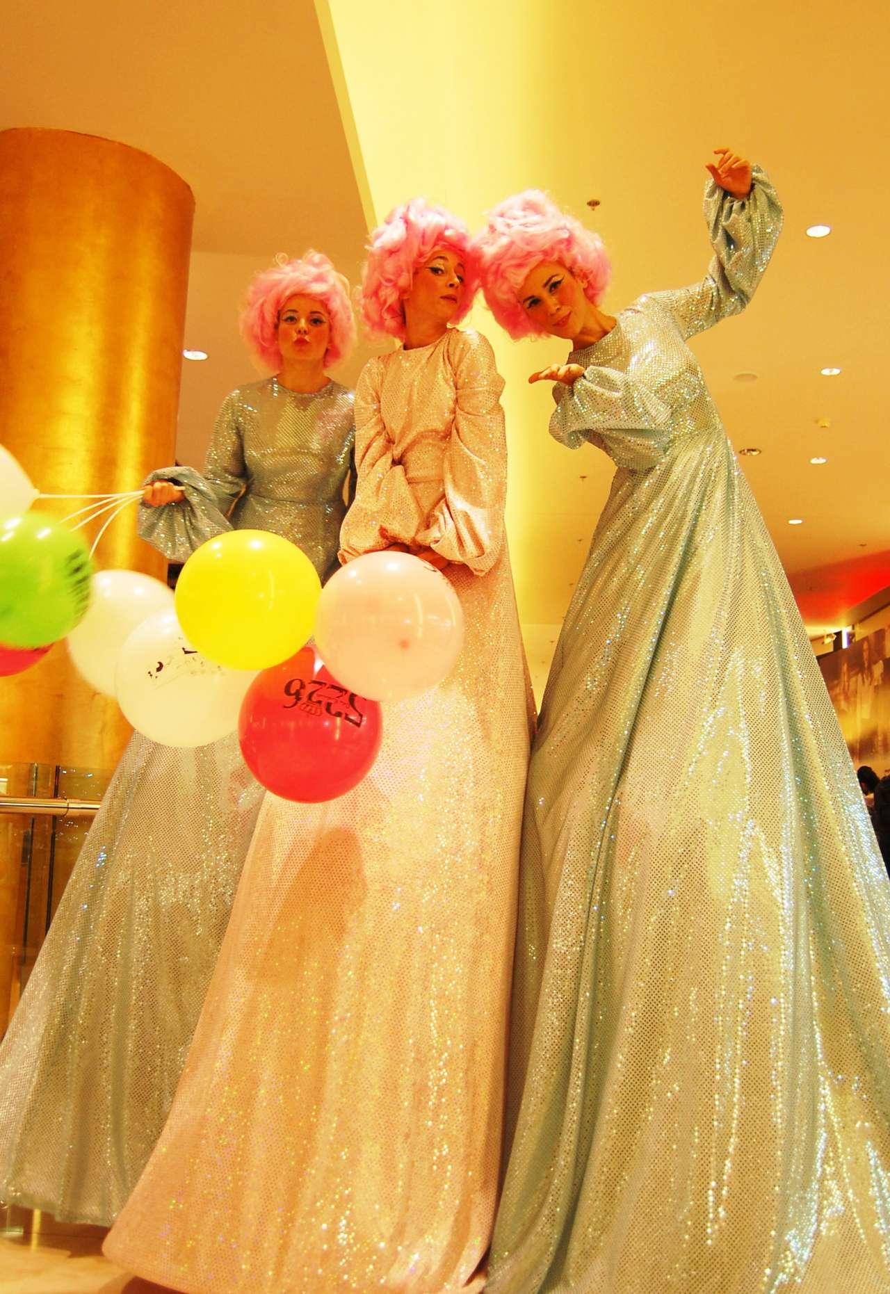 Τρεις ξυλοπόδαρες με ροζ περούκες και όμορφα μακριά φορέματα στα εγκαίνια του καταστήματος 5226 της Celia Kritharioti στο Golden Hall.