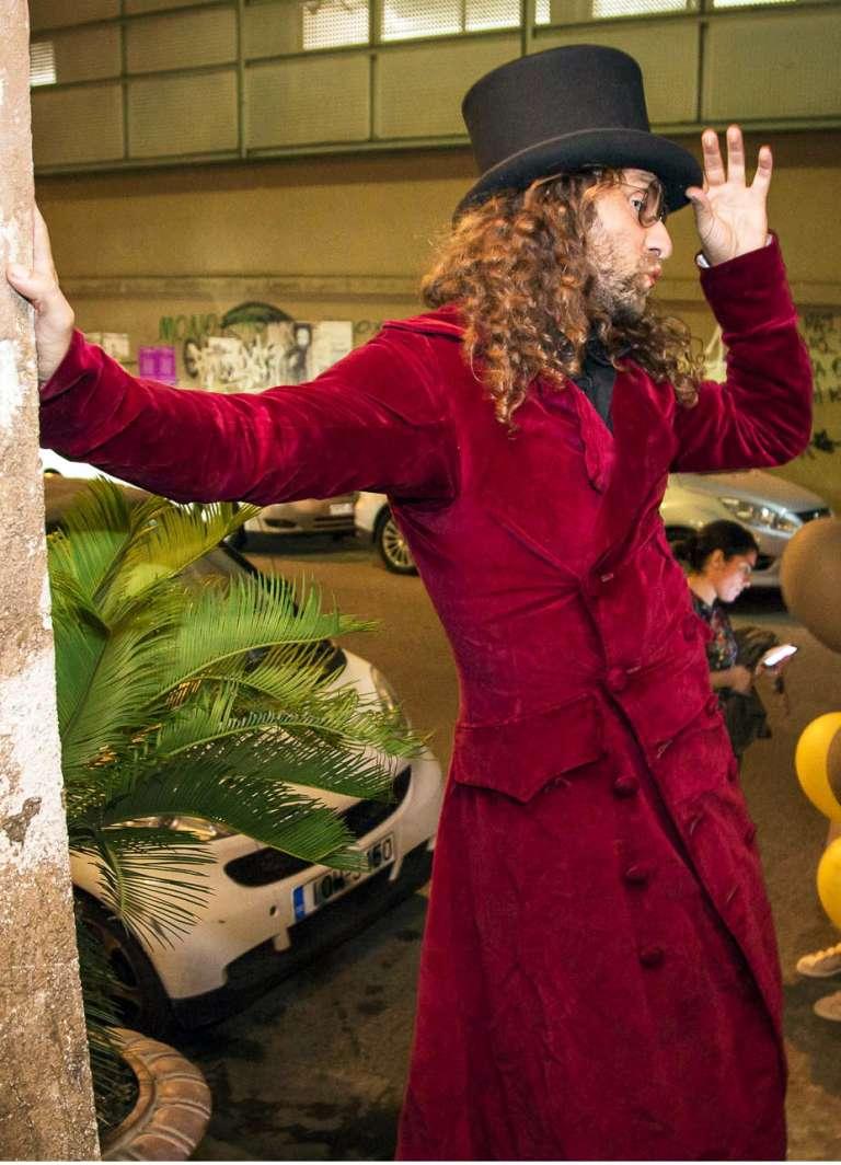 Ξυλοπόδαρος με μακριά σγουρά μαλλιά, ημίψηλο καπέλο και κόκκινο φράκο και ένα αυτοσαρκαστικό βλέμμα σε πάρτυ