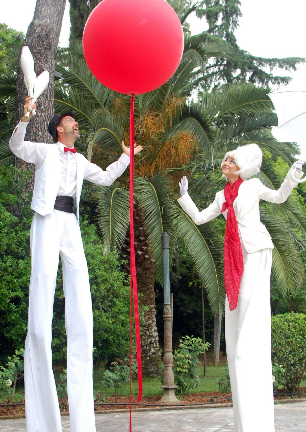 Ζευγάρι ξυλοπόδαρων, άντρας γυναίκα, με λευκά κοστούμια παίζουν με μεγάλο κόκκινο μπαλόνι σε πάρτι βάφτισης