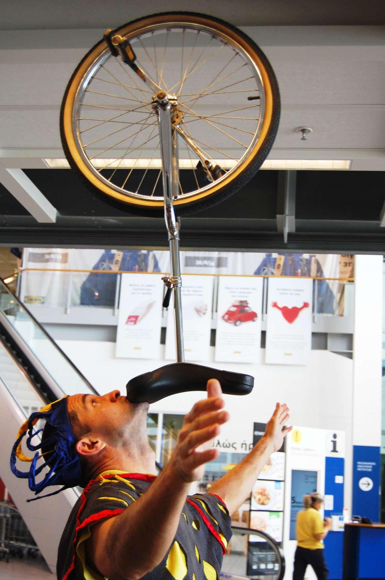Ζογκλέρ ισορροπεί μονοποδήλατο στο σαγόνι του σε παιδική εκδήλωση