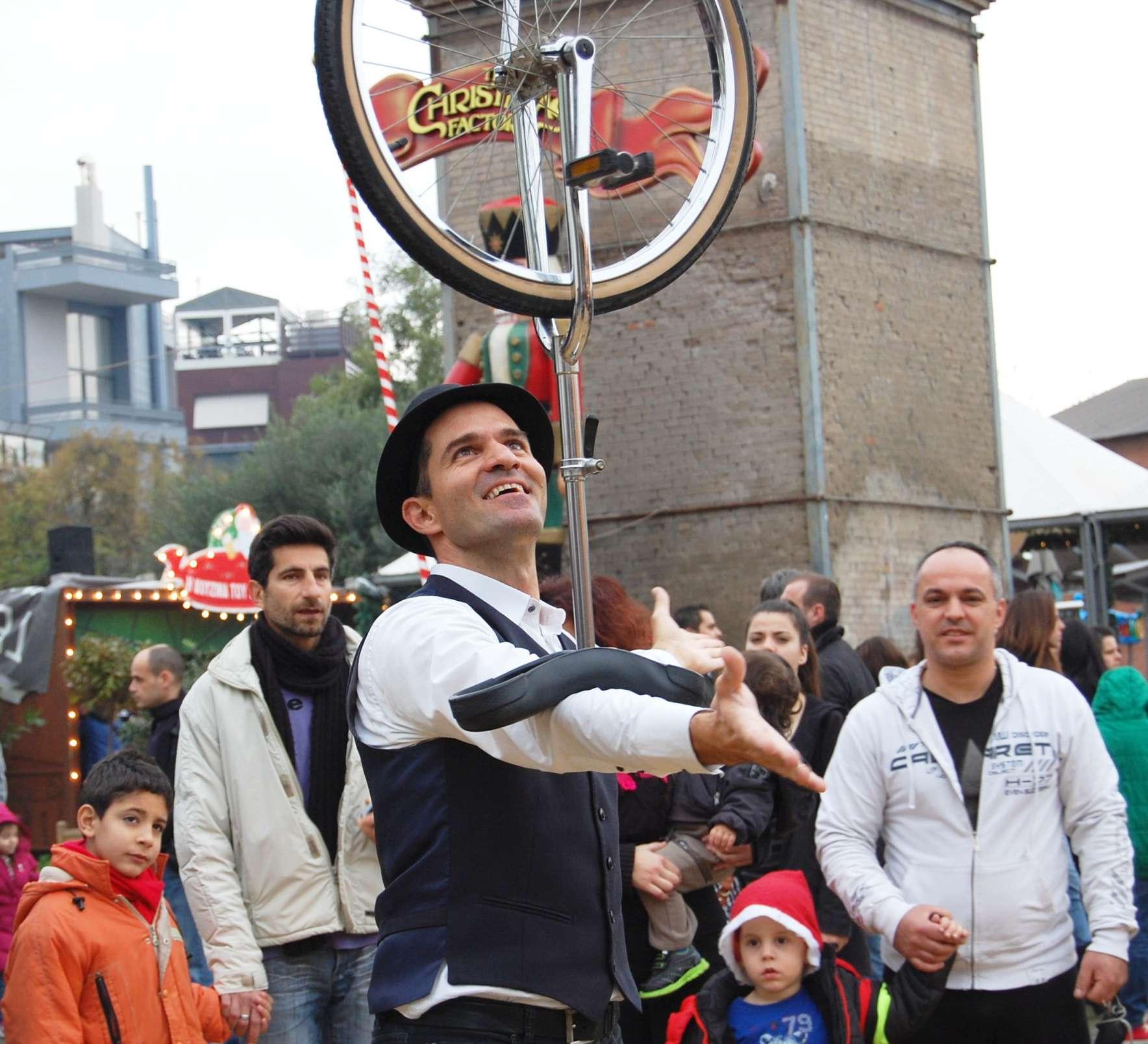 Ζογκλέρ ισορροπεί μονοποδήλατο στο χέρι του μπροστά σε κοινό σε Χριστουγεννιάτικο Χωριό
