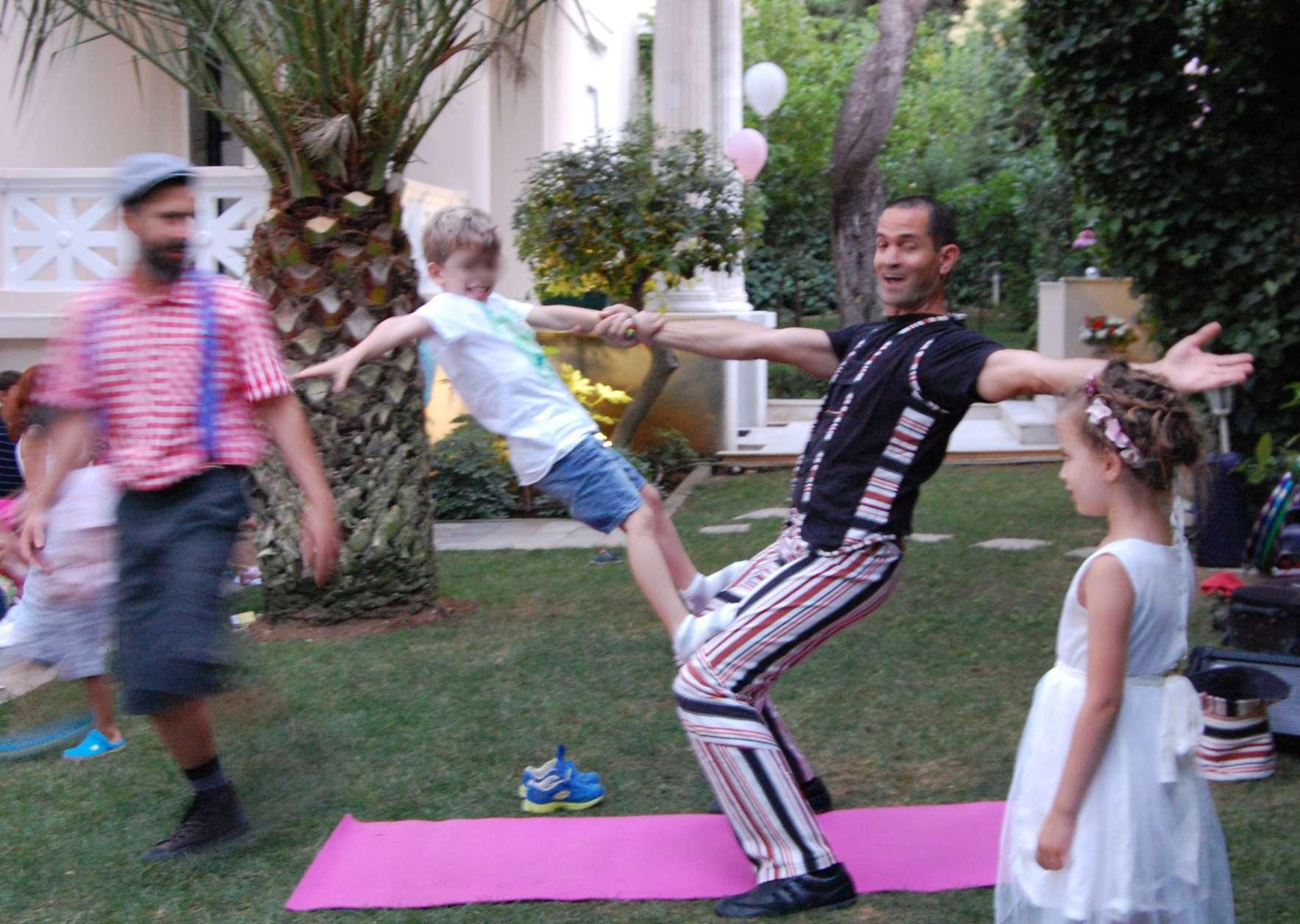 Ανιματέρ και αγόρι σε παιδικό πάρτυ παρουσιάζουν ακροβατική άσκηση ισορροπίας
