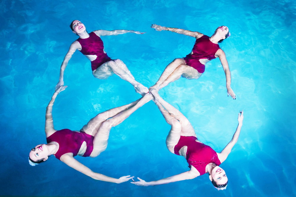 Four female athletes form a flower during a synchronised swimming show in a swimming pool.