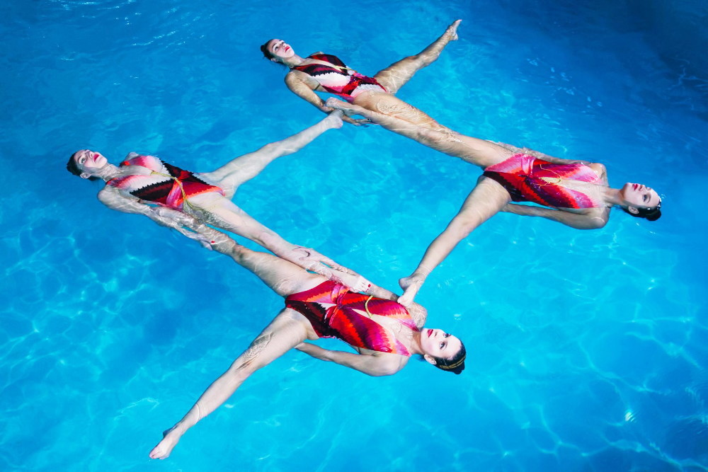Four female athletes form a square during a synchronised swimming show performed in a swimming pool.
