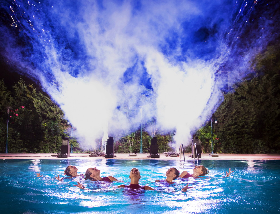 Synchronised Swimming show performed by five female athletes in a swimming pool.